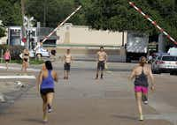 Trey Kubacak and Don Walker wait as Audra LeBeau and Julianne Kennedy, all of the CrossFit Dallas Central team, run 100 meter sprints.