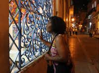 Credo Choir member Mattie Jette peers at the art in a Havana storefront.( Joy Tipping  -  Staff )