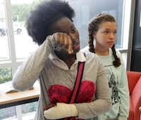 Tri'ana Jackson,13, left, wipes a tear away as she and Ciarrah Bryson, 14, explain security concerns at the school, as they attended a community meeting between DISD and parents at Dade Middle School on May 13, 2015. (Michael Ainsworth/The Dallas Morning News)