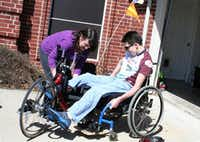 Lisa Dagley helps Alex Dagley, 27, onto his bike for some practice riding near their Frisco home. Alex and his brother Jason, 29, both were diagnosed with Friedreich's ataxia as children.(Ruth Haesemeyer - Special Contributor)
