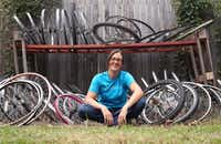 Rachel Spire sits with a collection of used bicycle wheels at her house in Grapevine October 16, 2012.