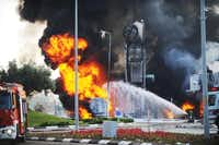 Israeli firefighters worked  to extinguish flames at a gasoline station in the Mediterranean port city of Ashdod after it was hit by a rocket fired from Gaza on Friday.(Avi Roccah - The Associated Press)