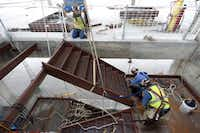 Construction workers install part of a stairwell on the 16th floor of the new Parkland hospital.