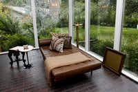 The sunroom, with floor-to-ceiling windows, is sparely furnished with a Mies van der Rohe chaise longue.