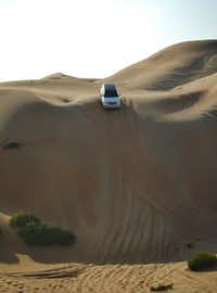 A professional driver from the Arabian Nights Village hotel in the United Arab Emirates takes visitors through the desert on a wild ride up and down dunes as high as 100 feet.