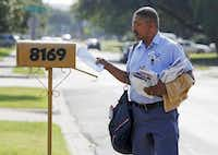 Jonathan O'Hara, a letter carrier for the U.S. Postal Service, delivers mail on his route along Green Hollow Lane in Dallas. The number of letter carriers has dropped across the country from a high in 1989 of 240,000 to around 190,000 in recent years, said Jim Sauber, chief of staff for the National Association of Letter Carriers.( Brandon Wade  -  Special Contributor )