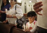 Evelin Garcia, 4, along with (from left) her mother, Esthela Estrada; her grandmother, Josofen Alvers; and her brother, Efren Garcia, prayed for Ebola patients and caregivers at The Cathedral Shrine of the Virgin of Guadalupe in Dallas on Thursday.( Andy Jacobsohn  -  Staff Photographer )