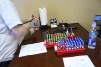 "Store owner Frank Malara rearranges the display at The Vapor Zone's tasting table. Malara said he sees the tasting table as a social way to try new e-cigarette solutions, ""like a hookah lounge.""Staff photo by DANIEL HOUSTON"