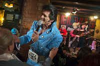 John Ehrenberger (center), performing as Elvis Presley impersonator Johnny Rockit, serenades Mary Duncan of Garland at El Ranchito restaurant Wednesday, January 8, 2014 in Dallas. For the last decade, the Oak Cliff eatery has spent the month of January hosting various Elvis-related performances.