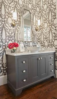 A bold wallcovering from Schumacher creates instant interest and drama in a guest bathroom. This space was designed by Emily Hewett of A Well Dressed Home.(Nate Rethlander)