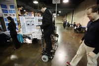 "Electrical engineer Paul Hylander, right, watches as Bishop Lynch student Matthew Whitby, 16, rides his version of a Segway called a yaryar, which means ""smaller"" in Somali, according to Whitby, during the 2014 Dallas Regional Science and Engineering Fair."