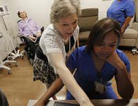 Tony Wood's wife, Janel (center), went over his medical history with nurse Natasha Jones on a recent visit to UT Southwestern Medical Center, where he goes twice a week for his one-man research trial.
