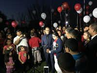 At center, community activist and family spokesman Carlos Quintanilla stands with Jose Cruz's cousin, Nora Rubi, as she addresses friends and family outside the Hughes Funeral Home on Wednesday night. (Julieta Chiquillo/Staff writer)