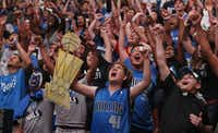Kevin Gonzalez, left, and Ricky Pacheco, center, cheer as the Mavs run the clock out to win the game during the watch party at the American Airlines Center in Dallas for Game Six of the NBA Finals between the Dallas Mavericks and the Miami Heat in Miami on Sunday, June 12, 2011.