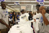 Robert Walker of Dallas (center), shows off his new championship t-shirt that he waited over an hour in line to purchase at the Academy Sports + Outdoors store on Forest Lane in Dallas, Texas following their championship game on June 12, 2011.