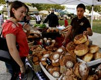 Ivan Paniagua, right, helps customer Erin Erwin of Rockwell with a selection of bread at the Rockwall Farmers Market in Rockwall, Texas, Saturday, May 7, 2011.