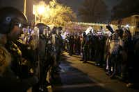 Police officers stood guard as protesters reacted to the announcement of the grand jury decision on Monday night in Ferguson, Mo. Police departments in several major cities said they were bracing for large demonstrations.(David Goldman - AP)
