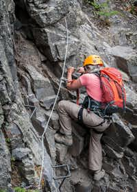 Dianne Leeth uses ladder rungs to work around an obstacle on Telluride's Via Ferrata.  While not always necessary, they make traversing the route faster and safer.