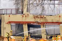 Firefighters water down the remains of a two-story building in the Sylvan Thirty development west of downtown Dallas. A Sylvan Thirty spokesman said the structure was to have housed a restaurant and a yoga studio.Photos by Kye R. Lee  -  Staff Photographer