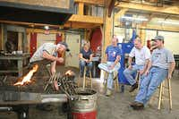 Blacksmithing students watch an instructor at work at John C. Campbell Folk School in Brasstown, N.C.