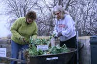 Lisa Ingalls (left) and Terri Barrett add to The Giving Garden's compost pile.(Staff photo by ELIZABETH KNIGHTEN - Neighborsgo)