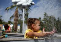 """Katelyn Nutt, 3, washes her hands in a """"rain cloud"""" in the Running River exhibit at the new Rory Meyers Children's Adventure Garden at the the Dallas Arboretum and Botanical Garden."""