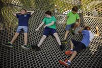 David Burke (left), Jackson Murtha, Houston Hall and Jason Fowler of Heritage Christian School lay in the netting of a large treehouse during a summer preview day at the new Rory Meyers Children's Adventure Garden at the Dallas Arboretum.