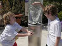 George Smith, 8, (left) tries out a water vortex machine as his cousin, Max Freele,8, looks on in the Kaleidoscope Gallery in the Dallas Arboretum's new Rory Meyers Children's Adventure Garden.