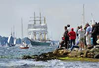 "Visitors watch the ""Alexander von Humboldt II"" tall ship at the Windjammer Parade of tall ships on June 23, 2012, in Kiel, Germany. The parade, which features approximately 100 tall ships and traditional large sailing ships, is the highlight of the Kieler Woche annual sailing festival."