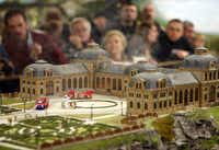 "Visitors look at an animated scenery of fire fighting vehicles arriving at a burning castle at the ""Miniatur-Wunderland"", or Miniature Wonderland, in Hamburg, northern Germany. It's billed as the world's largest model train set, a miniature world that snakes along eight miles of track, amid fields, cities, even the snowcapped Swiss Alps."