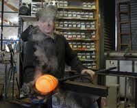 David Gappa, owner of Vetro Glass Blowing Studio in Grapevine, shapes a piece of molten glass into a rondel while using a wet newspaper to help cool and shape the glass.
