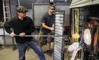 David Gappa, left, owner of Vetro Glass Blowing Studio in Grapevine, places a piece of glass in a furnace to heat at 2100 degrees so it can be shaped. Spencer Crouch, a glass blower works with David.