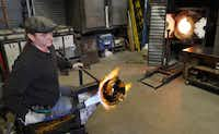 David Gappa, owner of Vetro Glass Blowing Studio in Grapevine, shapes a piece of glass into a rondel while using a gas fire torch.