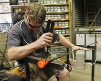 Glass blower Spencer Crouch uses tweezers to twist the color in the molten glass.