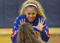 """The Harlem Globetrotters' Joyce """"Sweet J"""" Ekworomadu demonstrates a good ready stance for catching the basketball during a visit to Holy Family of Nazareth School in Irving."""