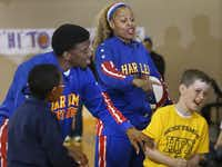 """The Harlem Globetrotters' Joyce """"Sweet J"""" Ekworomadu and teammate Anthony """"Buckets"""" Blakes refereed a friendly game of """"Rock. Paper, Scissors"""" between fourth-graders Immanuel Brinson (left) and Charlie Woertendyke during a visit to  Holy Family of Nazareth School in Irving on Monday."""