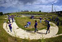 FedEx volunteers planted native grass and plants along the Santa Fe Trestle Trail and Trinity River, Friday, April 27, 2012 as part of an effort  to clean up and beautify  the area which begins the Great Trinity Forest as part of the Trinity Corridor Project. Downtown Dallas can be seen across the Trinity River.