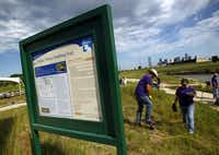 FedEx volunteers planted native grass and plants along the Santa Fe Trestle Trail and Trinity River, Friday, April 27, 2012 as part of an effort  to clean up and beautify  the area which begins the Great Trinity Forest as part of the Trinity Corridor Project. The sign welcomes visitors to the Dallas Trinity Paddling Trail.
