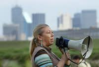 Judy Schmidt of the City of Dallas uses a bullhorn to welcome FedEx volunteers who planted native grass and plants along the Santa Fe Trestle Trail and Trinity River, Friday, April 27, 2012 as part of an effort  to clean up and beautify the area which begins the Great Trinity Forest as part of the Trinity Corridor Project.