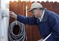 PG&E employee Art Liscano, 66, reads a meter at a house in Clovis, Calif. Every day, PG&E replaces 1,200 old-fashioned meters with digital versions that can collect information without human help and generate more accurate power bills.