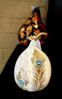 A peacock light (front) with a bronze paisley light made from a gourd by sisters Cathy Neumeyer and Linda Moore of Le Gourd on Blue