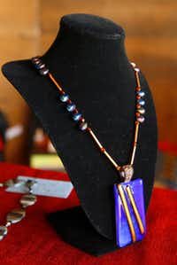 Dark blue copper fused with fired glass in this four stage on copper with sapphire stones created by Kay LeMere of Exotic Gems and Jewels at the Handmade Arts Market in Dallas, Saturday, Sept. 1, 2012.