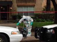 An employee in a hazmat suit works in front of the apartment building.(Melissa Repko - Staff)
