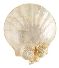 Shell game: A luminous capiz trinket holder accented with genuine seashells accessorizes the dressing table or bath counter. Holder is 4 inches in diameter; $52 at Showcase Home Decor, Dallas.