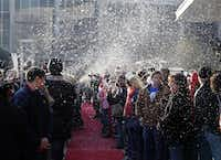 Hundreds of volunteers wait on the red carpet for 500 homeless people to arrive at the Omni Dallas Hotel on Monday.