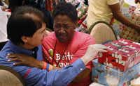 David Timothy, founder of the SoupMobil, gets a hug from Carol 'Mama' Hawkins, 58, after she receivied gifts and lunch at the Omni Dallas Hotel on Monday