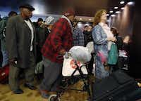 Carol 'Mama' Hawkins, 58, (center) waits in line to receive a backpack and clothes with other homeless people at the Omni Dallas Hotel on Monday.