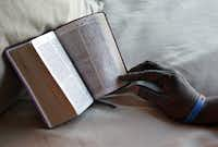 Carol 'Mama' Hawkins, 58, marks her favorite chapter in her Bible after placing it on her bed at the Omni Dallas Hotel on Monday.