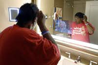 Carol 'Mama' Hawkins, 58, combs her hair in a mirror that has a built-in TV in the bathroom at the Omni Dallas Hotel on Monday.
