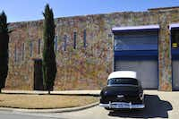A car sits parked outside of a painted house in the Deep Ellum district.
